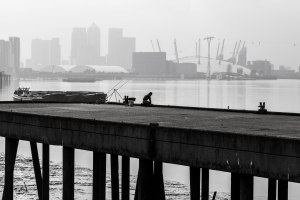 A fisherman on the river bank; the Dome and Canary Wharf offering a fitting backdrop with the haziness of the day.